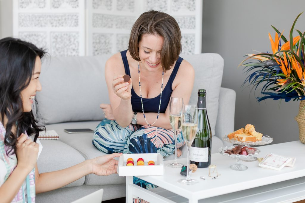 two women sitting on sofa laughing together with champagne and pralines